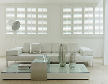 White Shutter blinds in a white living room with neutral pieces of furniture