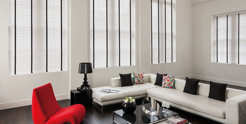 White and black venetian blinds in a white lounge with statement pieces of furniture