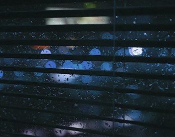 Dark Venetian blinds snapshot with rain in the background