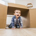 Little boy playing with a cardboard box at home