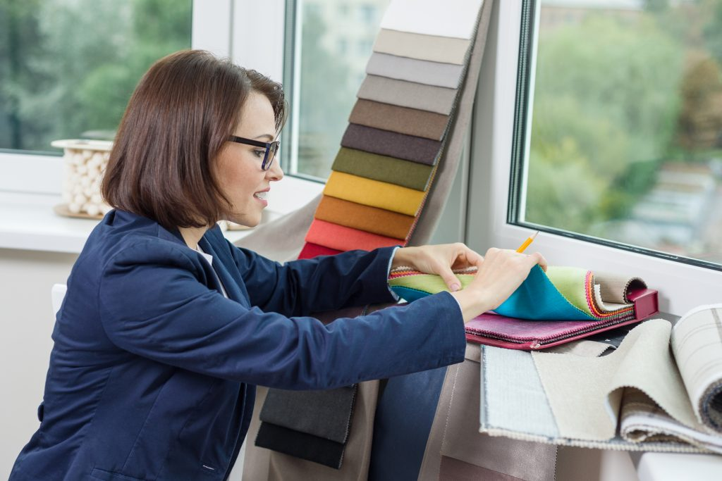 Woman interior designer, works with samples of fabrics for curtains and blinds. Business - textile industry.