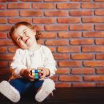 Cute little girl sitting in a room. Child have fun at home near wall. Little girl is studying a colorful cube