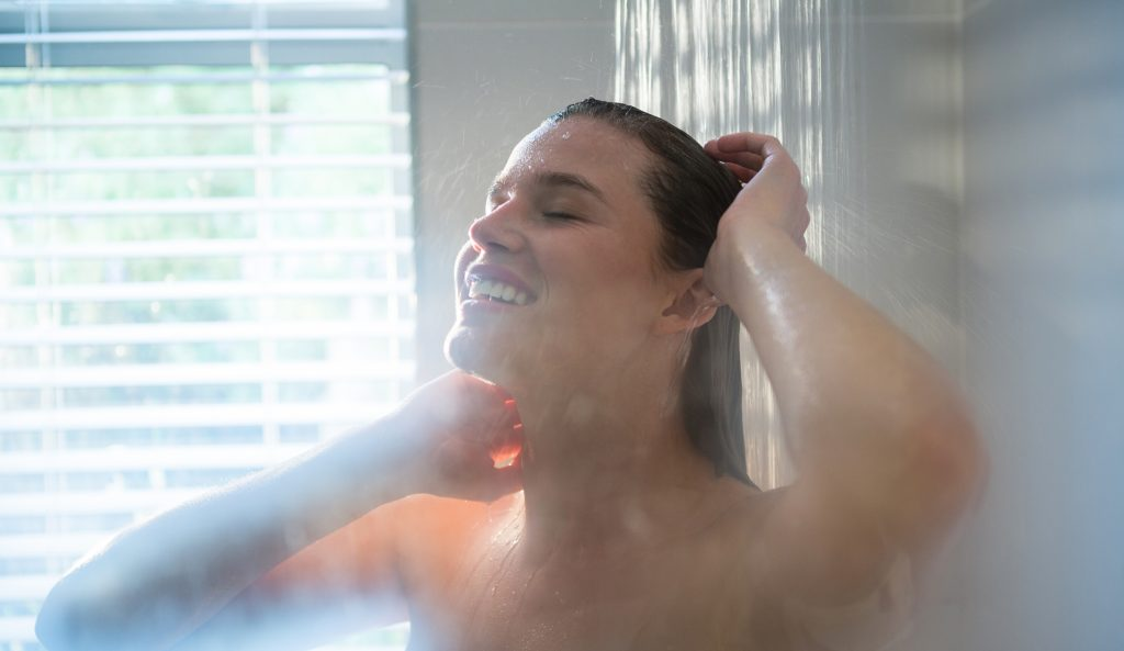 Woman taking a shower in bathroom at home