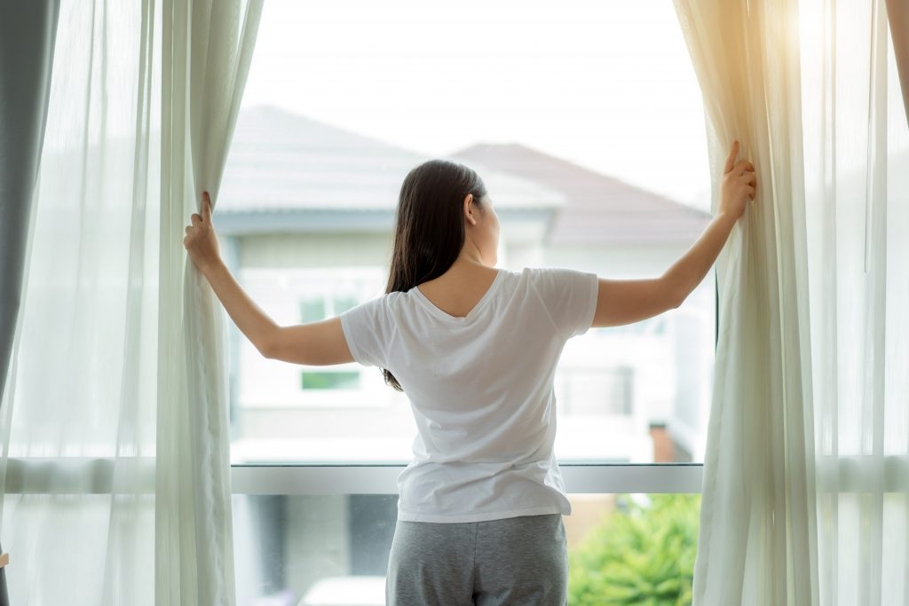 Rear view of Asian woman waking up in her bed fully rested opening window curtains and looking through the window in bedroom at home.