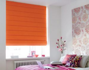 Bright orange roman blinds in a colourful bedroom