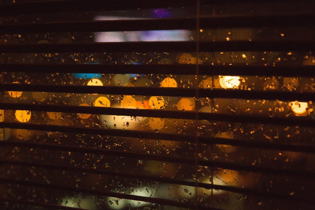 Dark Venetian blinds snapshot with rain in the background