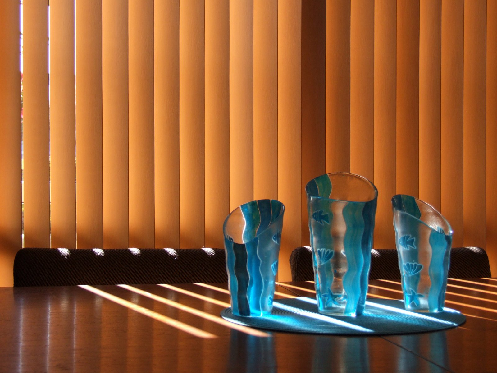 Sun peeping through vertical blinds in a dining area