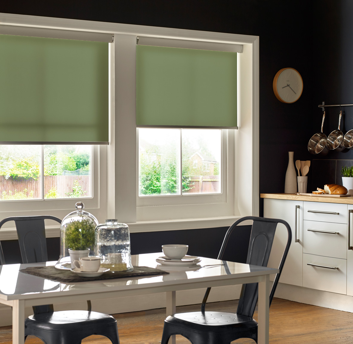 Window blinds Coventry. Green roller blinds in kitchen window. Dark walls and dining table.