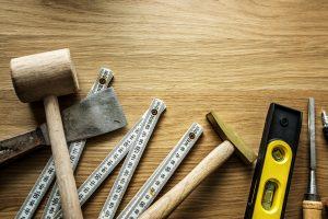 Flat lay of DIY tools on wooden floor.